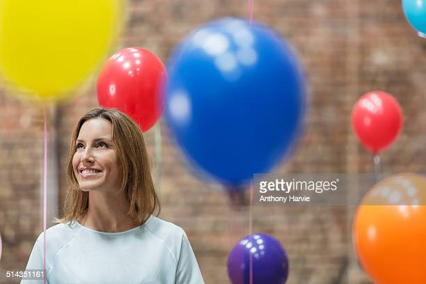 Smiling woman in warehouse with colourful balloons