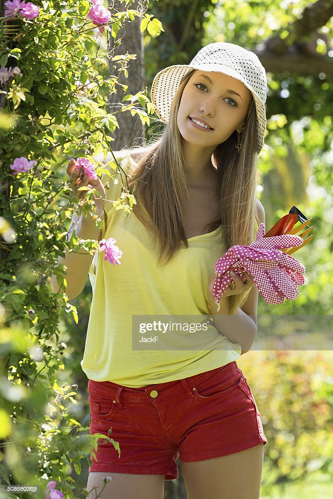 Smiling woman in yard gardening : Stock Photo