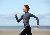 Profile portrait of a smiling woman jogging at the sea side