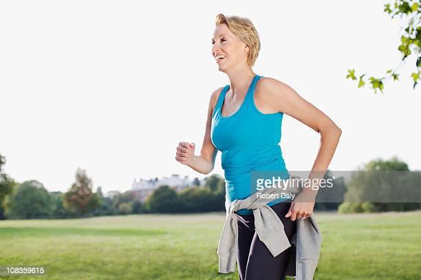 Souriant femme jogging dans le parc
