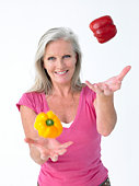 Smiling woman juggling peppers