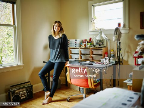 Smiling woman leaning against desk in home office