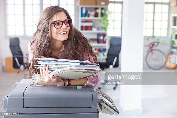 Smiling woman leaning on copy machine in workplace