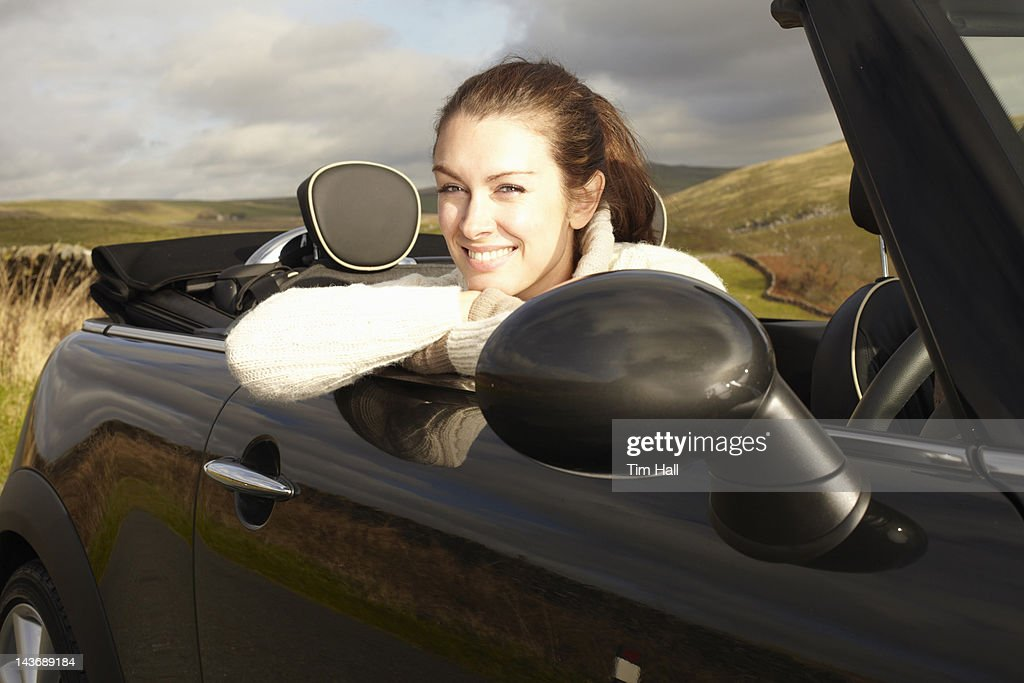 Smiling woman leaning out of convertible : Stock Photo
