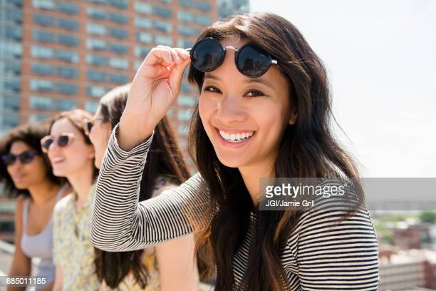 Smiling woman lifting sunglasses outdoors