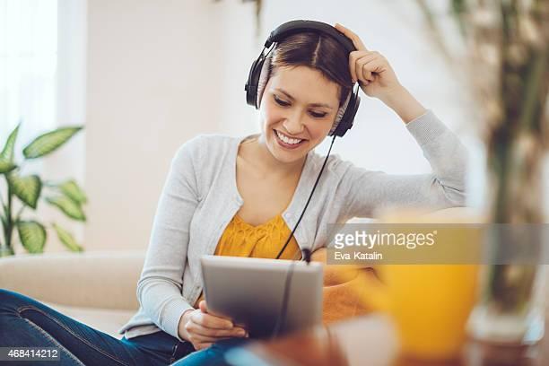 Donna sorridente ascoltando la musica a casa