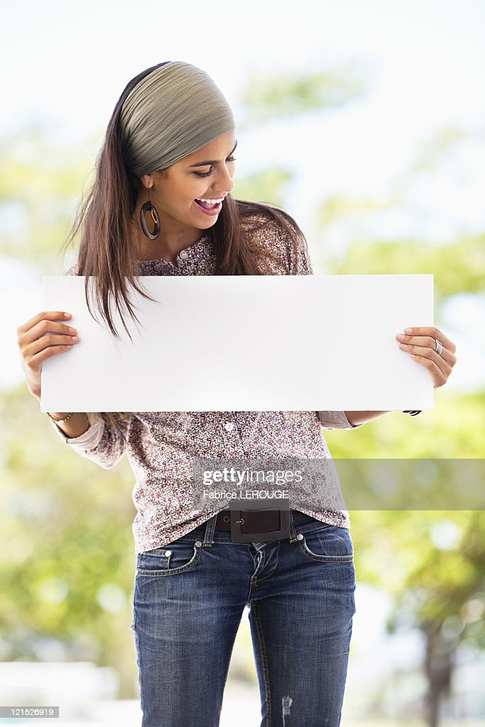 Smiling woman looking at a blank placard : Stock Photo