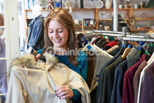 Donna shopping nel negozio di articoli di seconda mano guardando i vestiti    Foto stock 2ff9013d272