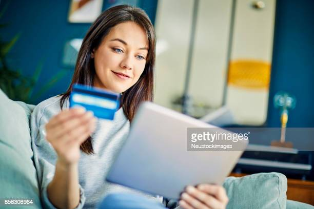 Smiling woman looking at credit card while using digital tablet