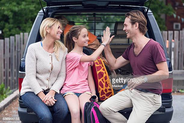 Smiling woman looking at father and daughter giving high-five in car trunk