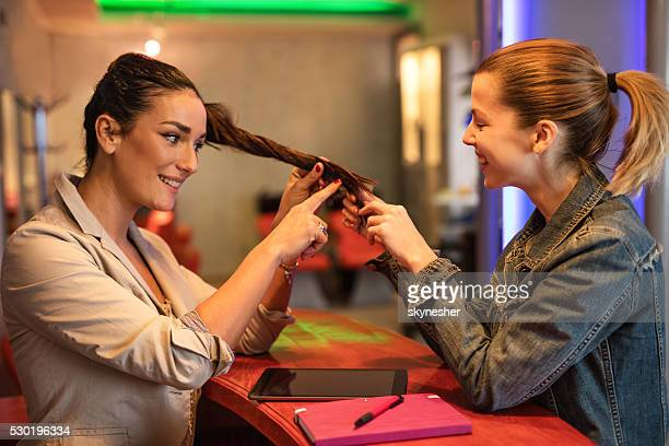 Smiling woman looking at friends hair at beauty salon.
