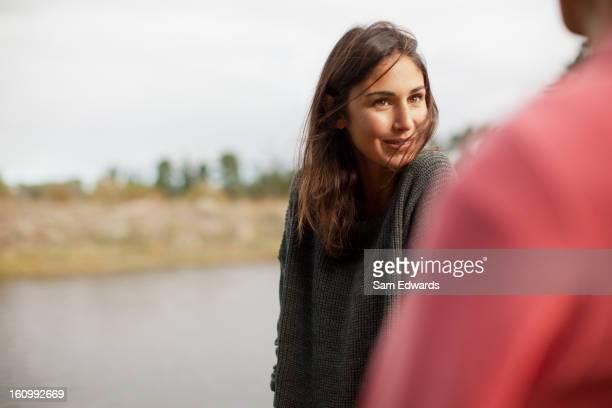 Femme souriante regardant l'homme au bord du lac
