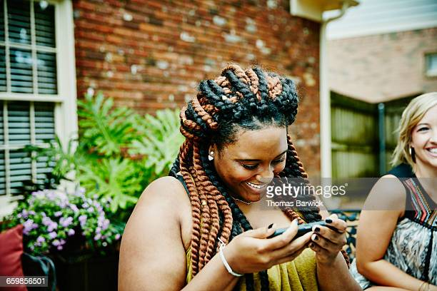 Smiling woman looking at photos on smartphone