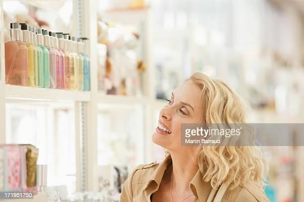 Femme souriante regardant de parfum du magasin