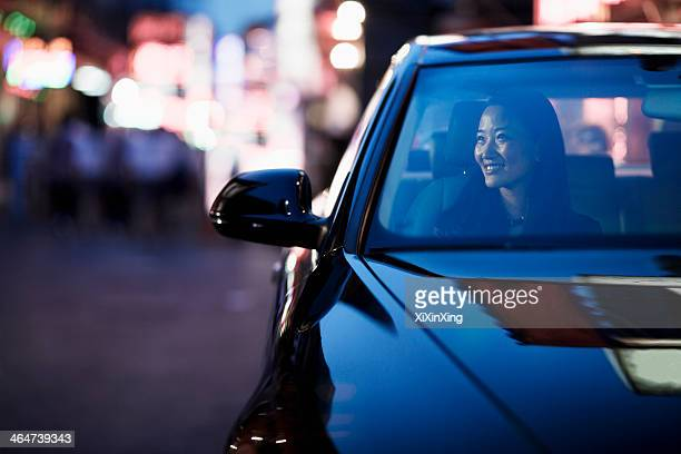 Smiling woman looking through car window at the city nightlife