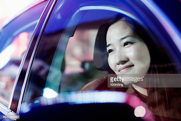 Smiling woman looking through car window at the city nightlife, reflected lights