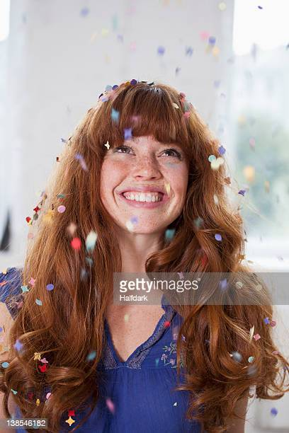 A smiling woman looking up at confetti falling