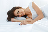 Young beautiful smiling woman lying in her bed  fully rested after wake up. Healthy lifestyle. Wellness concept