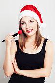 Smiling Woman Makeup Artist wearing Christmas Santa Hat