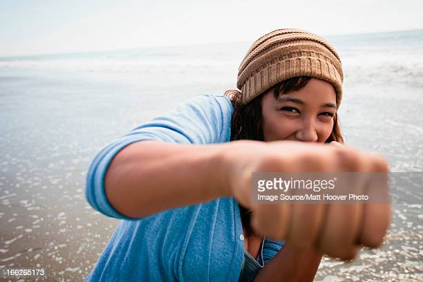Smiling woman making fists on beach