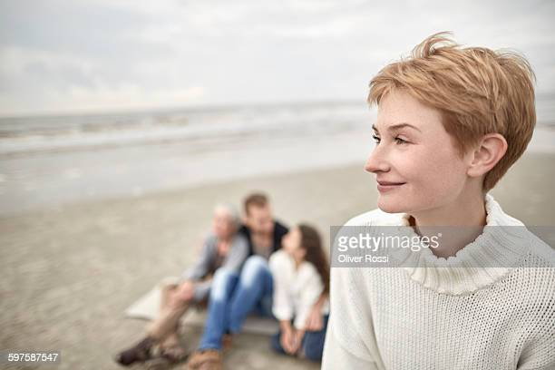Smiling woman on beach with family in background