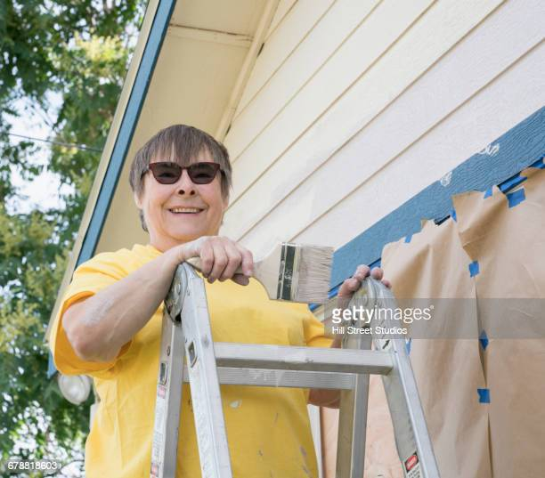Smiling woman on ladder painting house