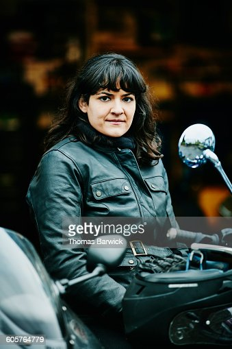 Smiling woman on motorcycle with helmet off