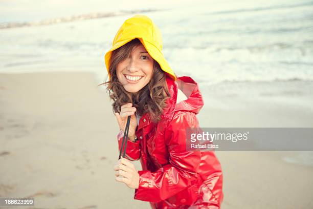 Smiling woman on the beach on a rainy day