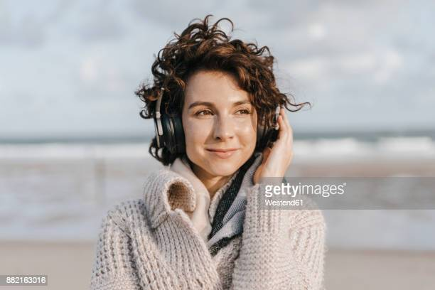 Smiling woman on the beach with headphones