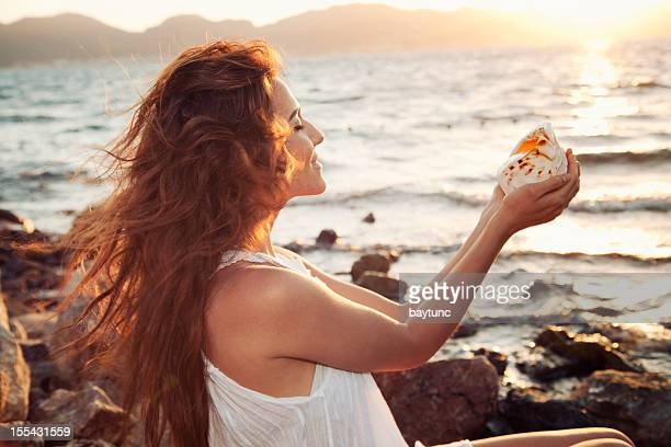 Lächelnde Frau am Strand mit seashell