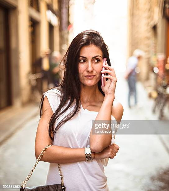 smiling woman on the city on the phone