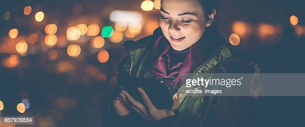 Smiling woman on the rooftop using tablet PC