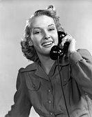 Smiling Woman On The Telephone Wearing A Long Sleeve Shirtdress With Cuffs & 2 Button Flaped Chest Pockets Warm Friendly Exuberant.
