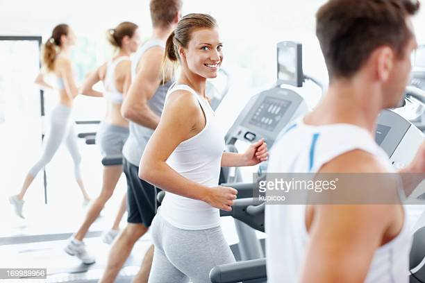 Smiling woman on treadmill alongside other members