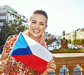 The spirit of old Europe in Prague. Portrait of smiling modern woman on Vaclavske namesti in Prague, Czech Republic showing flag