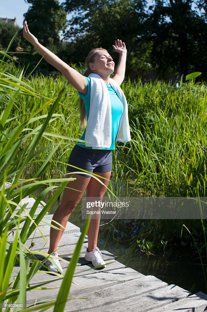smiling woman opening her arms wide for mindfulness, sunny outdoors : Stock Photo