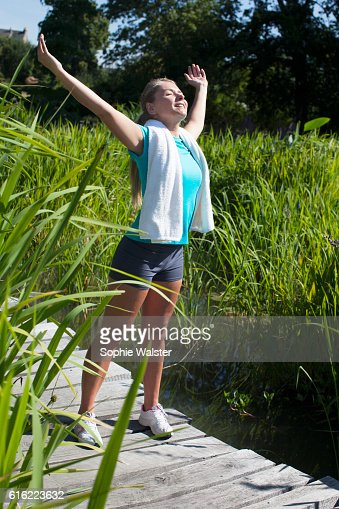 smiling woman opening her arms wide for mindfulness, sunny outdoors : Stockfoto