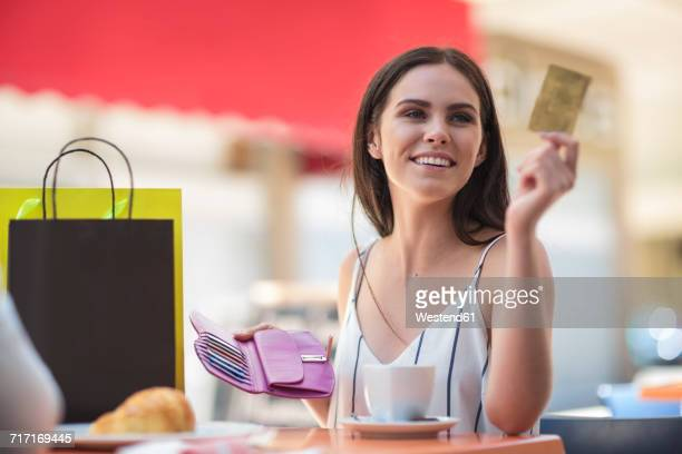 Smiling woman paying with credit card at cafe