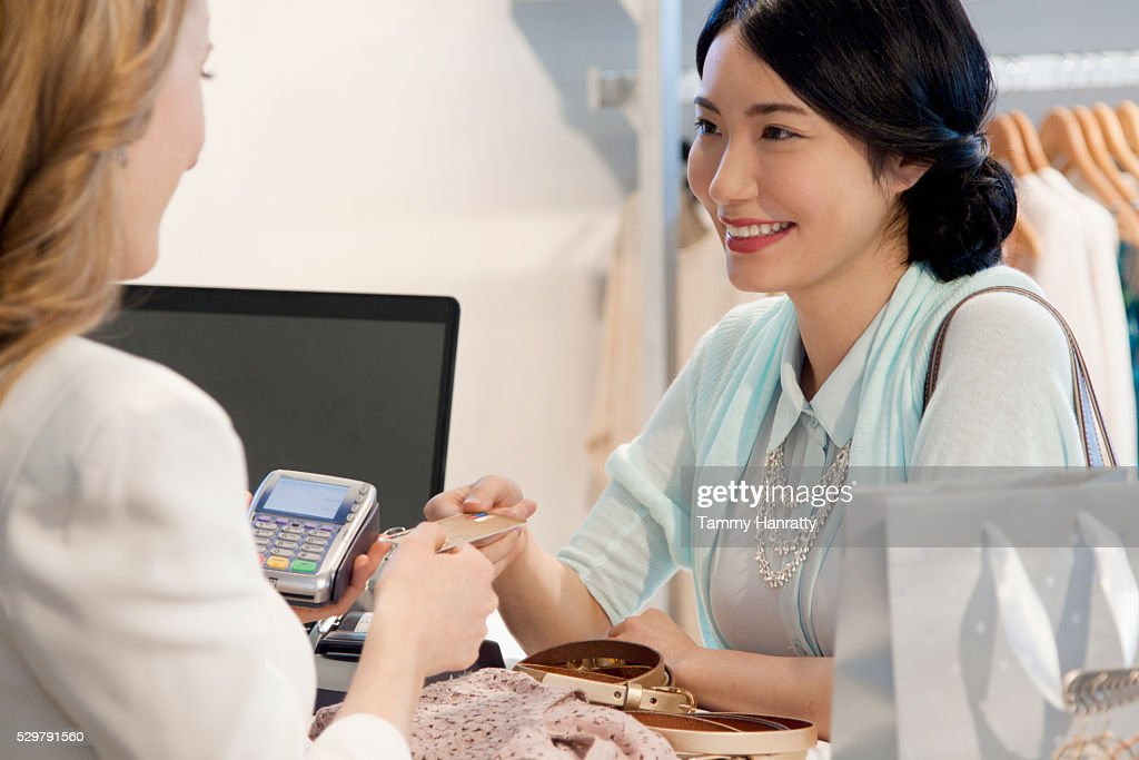 Smiling woman paying with credit card : Stock Photo