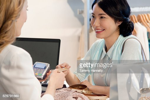 Smiling woman paying with credit card : Photo