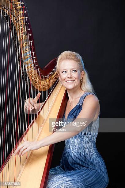 Smiling woman playing harp
