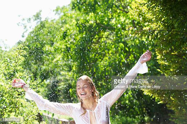 Smiling woman playing in rain shower