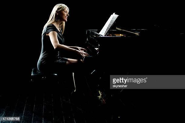 Smiling woman playing piano.