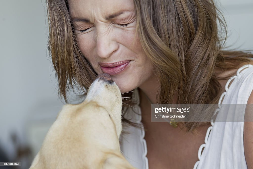 Smiling woman playing with dog : Stock Photo