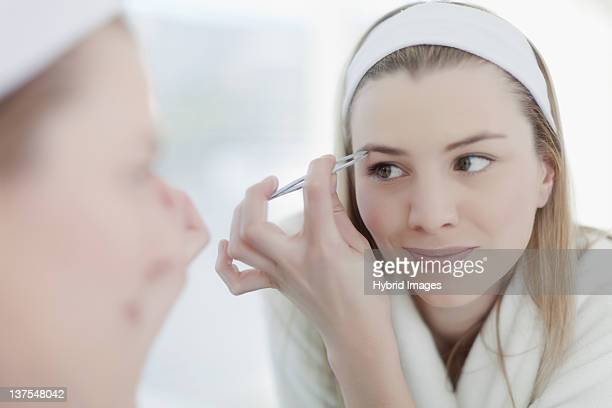 Smiling woman plucking her eyebrows