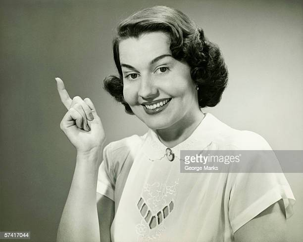 Smiling woman pointing finger in studio, (B&W), (Close-up), (Portrait)