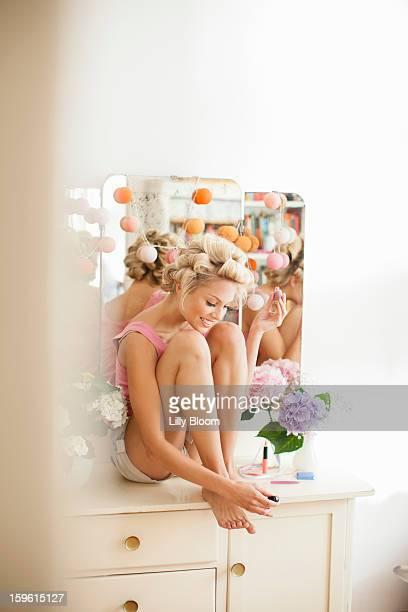Smiling woman polishing her toenails