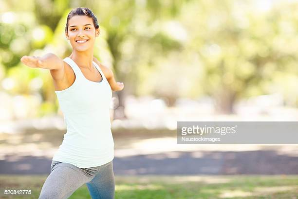 Smiling Woman Practicing Yoga In Warrior 2 Pose