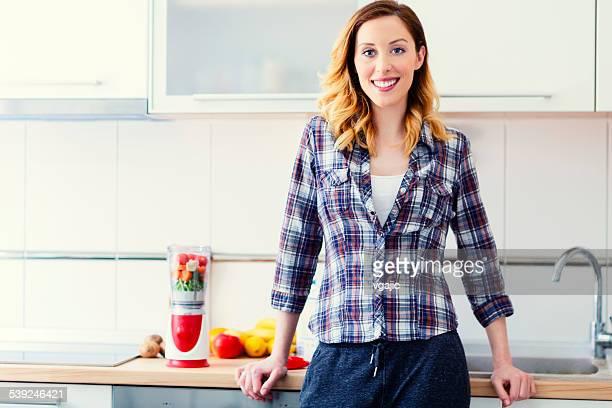 Lächelnd Frau Vorbereitung einen Smoothie.