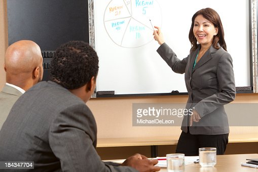 Smiling woman presenting a pie chart in front of two men